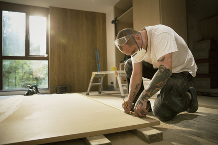 Construction worker with tattoos measuring and marking wood board in house