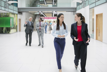 Businesswomen walking and talking in office lobby