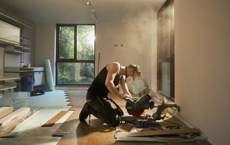 Construction worker using electric saw to cut hardwood flooring in house LANG_EVOIMAGES