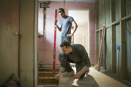 Construction workers using tape measure and level tool in house LANG_EVOIMAGES