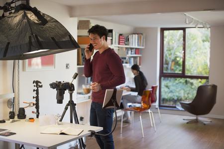 Male photographer working in studio, taking coffee break