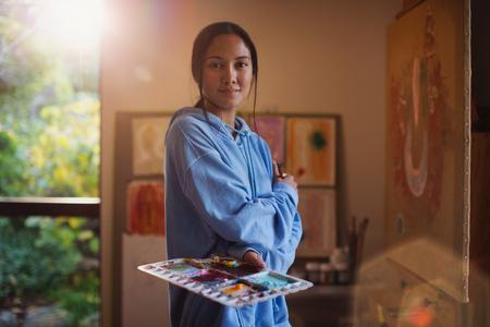 Portrait confident female artist painting in art studio LANG_EVOIMAGES
