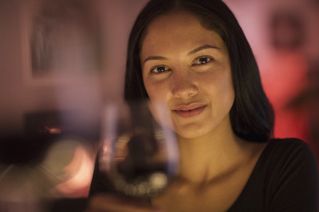 Portrait confident young woman holding wine glass