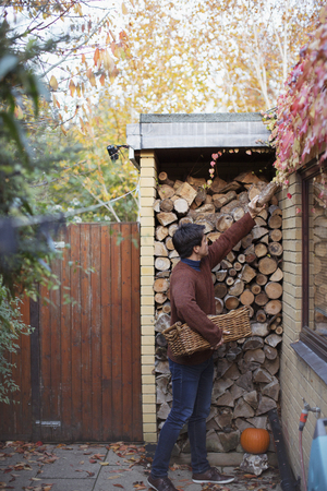 Man reaching for firewood on autumn patio LANG_EVOIMAGES