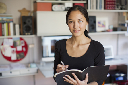 Portrait confident young woman working in home office LANG_EVOIMAGES