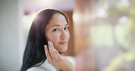 Portrait confident young woman applying moisturizer to face