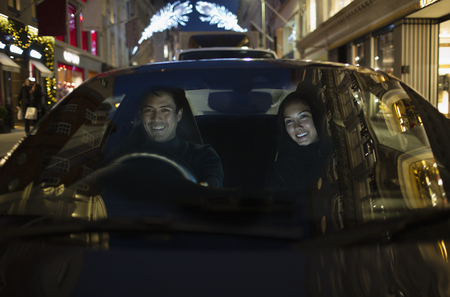 Smiling couple driving car at night LANG_EVOIMAGES