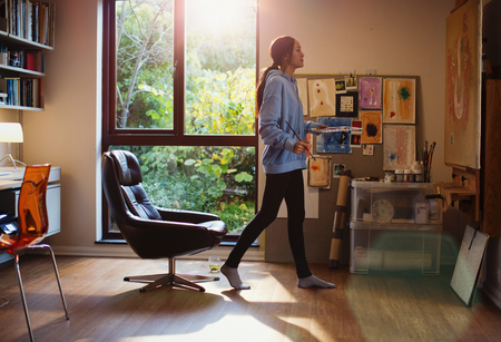 Female artist painting in home office