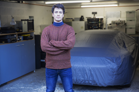 Portrait confident man standing in front of covered car in garage LANG_EVOIMAGES
