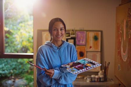 Portrait smiling female artist painting in art studio