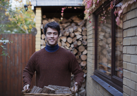 Portrait man carrying firewood on autumn patio LANG_EVOIMAGES