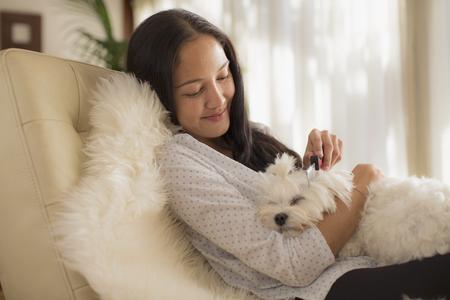 Smiling young woman brushing sleeping dog