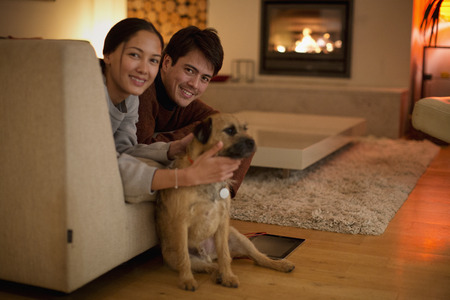 Portrait happy couple with dog in living room