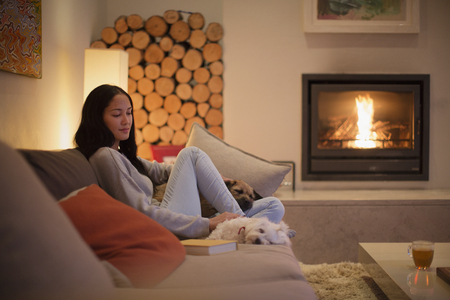 Young woman relaxing on sofa with dogs by fireplace
