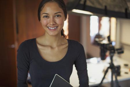 Portrait smiling, confident female photographer in studio