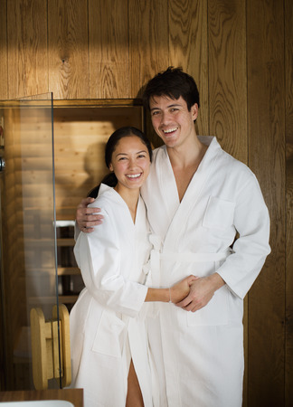 Portrait happy couple in bathrobes at spa