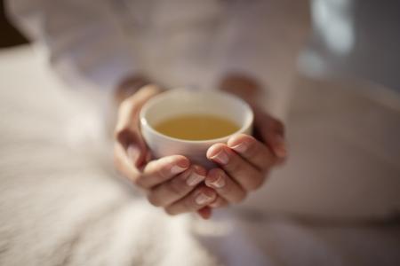 Close up woman cupping hot tea