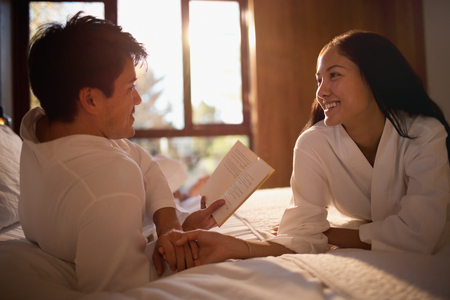 Couple in bathrobes reading book in bed