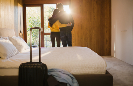 Couple with suitcase hugging in bedroom LANG_EVOIMAGES