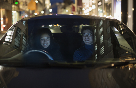Smiling couple driving on city street