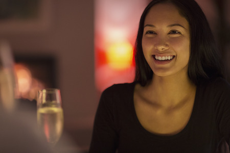 Happy young woman drinking champagne LANG_EVOIMAGES