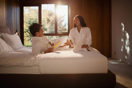 Couple in bathrobes relaxing on hotel bed