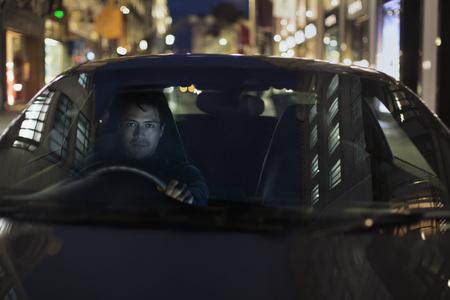 Portrait man driving car at night LANG_EVOIMAGES