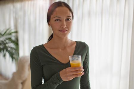Portrait confident young woman drinking orange juice