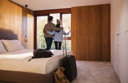 Couple with suitcase looking out bedroom window