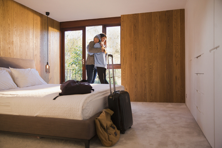 Happy couple with suitcase hugging in bedroom