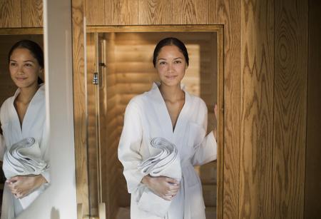 Portrait young woman in bathrobe standing in spa doorway
