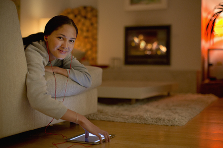 Portrait smiling young woman listening to music with headphones and digital tablet