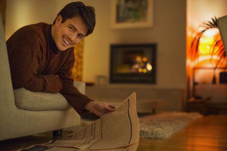 Portrait smiling man reading newspaper in living room