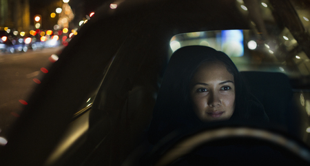 Young woman driving car at night LANG_EVOIMAGES