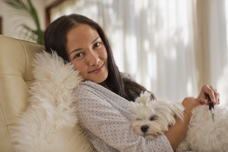 Portrait smiling young woman cuddling with dog LANG_EVOIMAGES