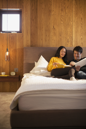 Couple reading book and using digital tablet in bed LANG_EVOIMAGES