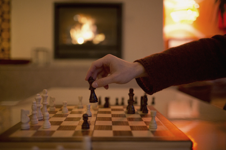 Hand playing chess, moving piece