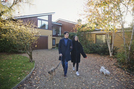 Couple walking dogs in autumn driveway LANG_EVOIMAGES