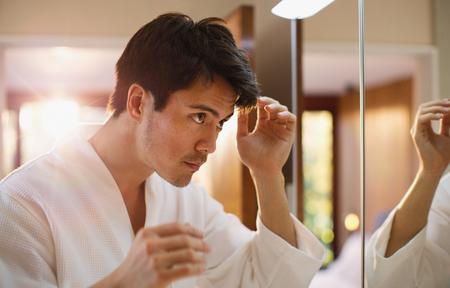 Man checking hair in bathroom mirror LANG_EVOIMAGES