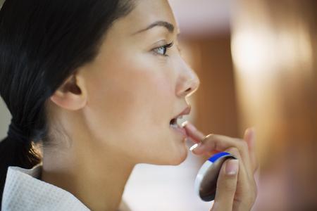 Close up young woman applying lip balm