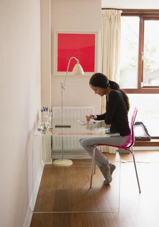 Young woman using digital tablet at desk LANG_EVOIMAGES