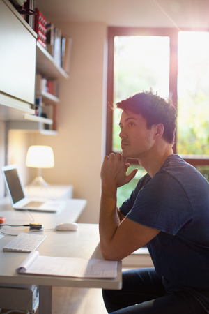 Thoughtful man working at desk in home office