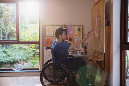 Male artist in wheelchair painting in art studio