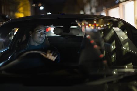 Man driving car at night LANG_EVOIMAGES