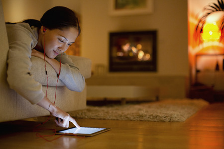 Young woman with headphones using digital tablet in living room