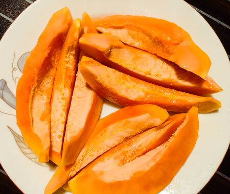 Papaya slices in a dish. With Black Backgrround.
