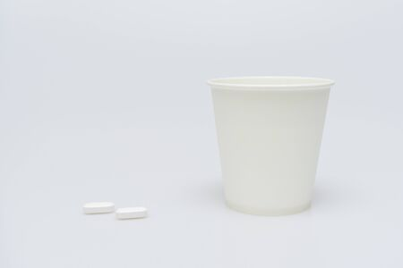 Paper cup with water and two pills