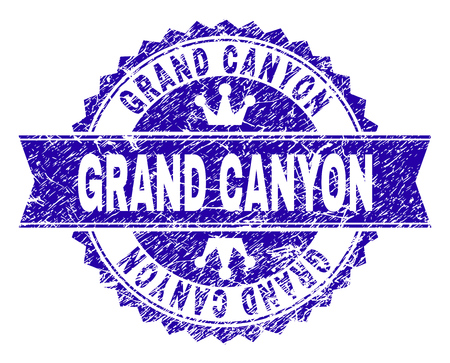 GRAND CANYON rosette stamp seal overlay with grunge texture. Designed with round rosette, ribbon and small crowns. Blue vector rubber watermark of GRAND CANYON caption with dust texture.