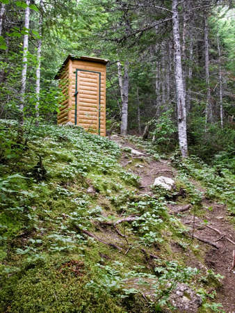 latrine: A stylish outhouse tucked neatly away on top of a hill.