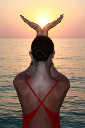 young woman holds sun in palms in Mediterranean Sea photo